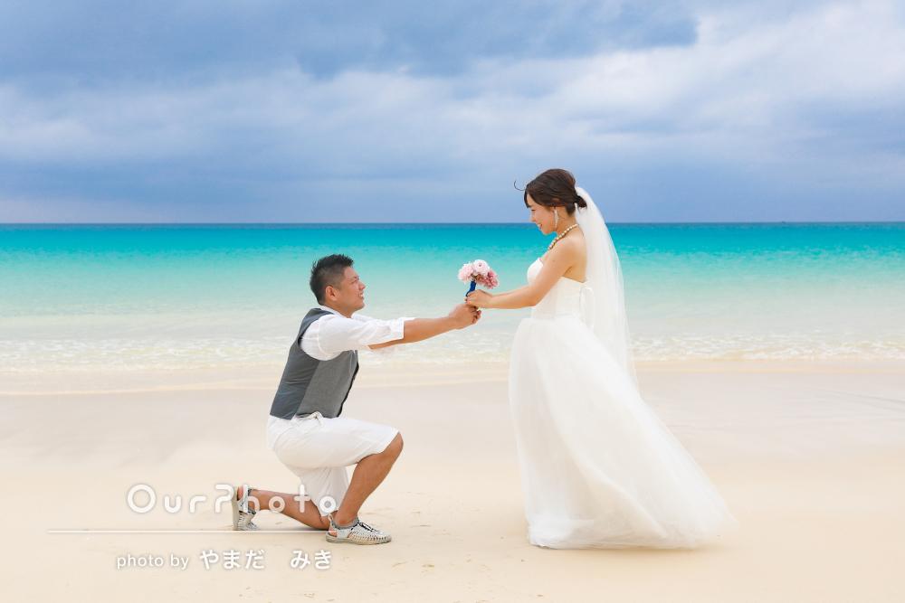 沖縄の鮮やかな色をした海を前に幸せな結婚記念のカップルフォトの撮影