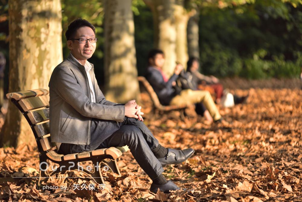 落ち葉がおおい尽くす公園で秋の落ち着いた雰囲気の男性プロフィール写真