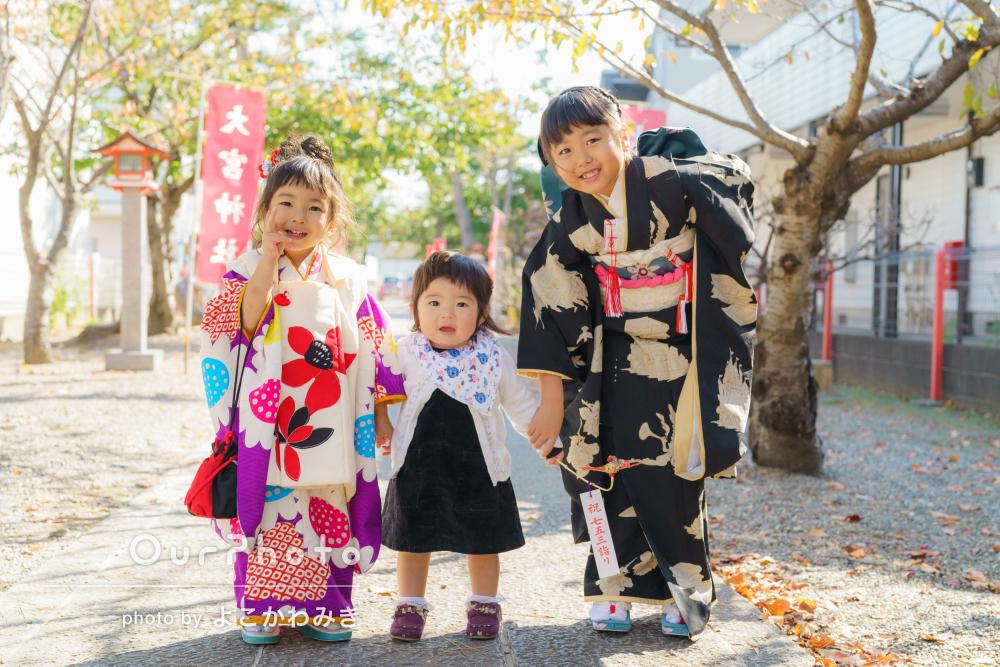 木漏れ日が降り注ぐ参道で三姉妹仲良く七五三詣りの撮影