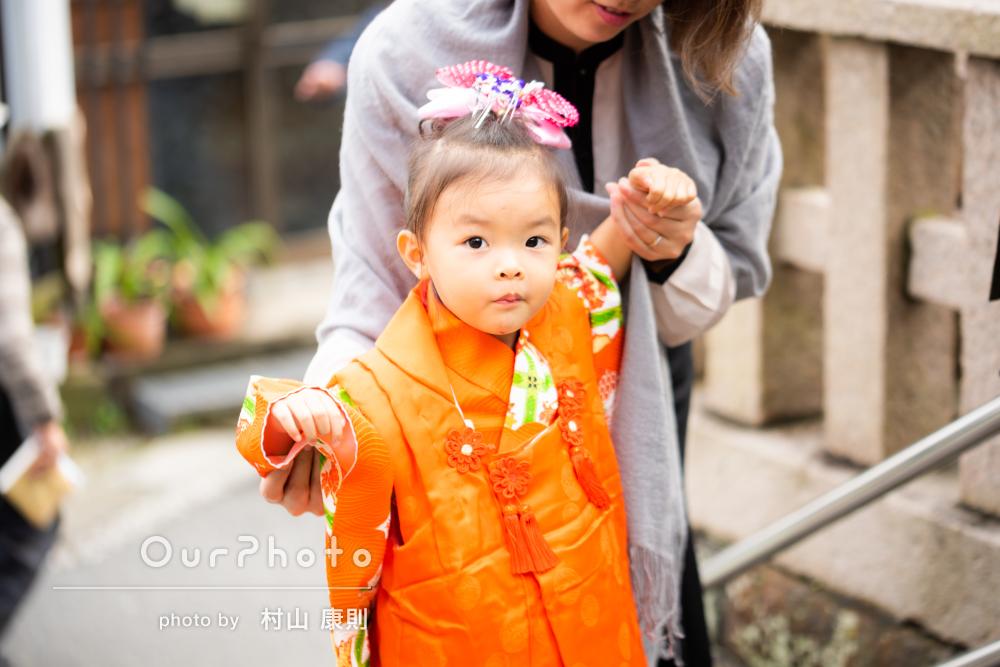 愛らしいオレンジ色の和装姿が緑あふれる神社に映える3歳の七五三の撮影