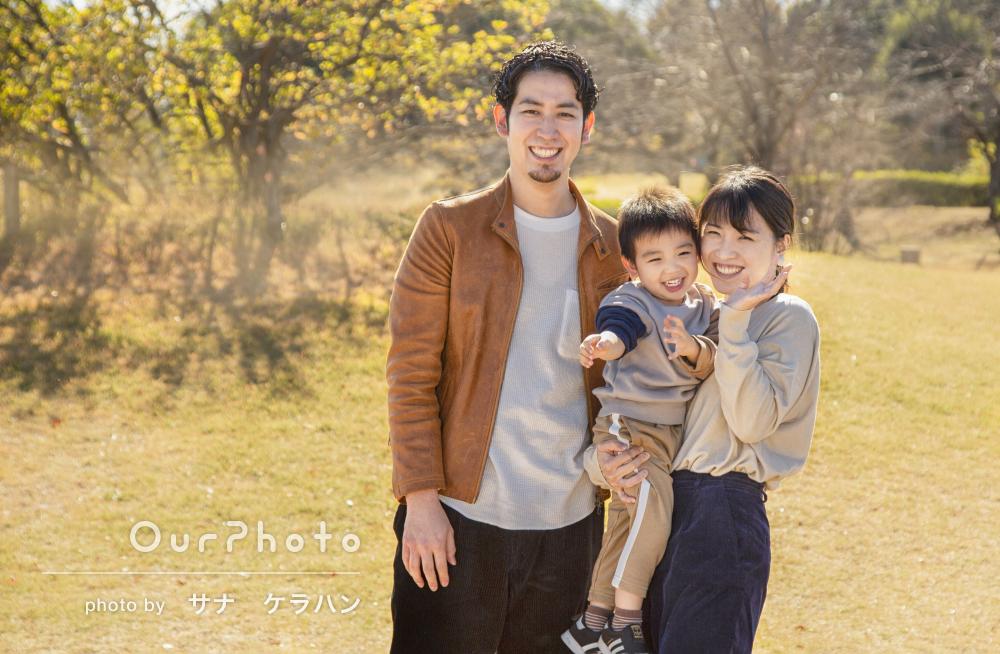 秋の広々とした公園で家族3人の自然体をとらえた家族写真の撮影