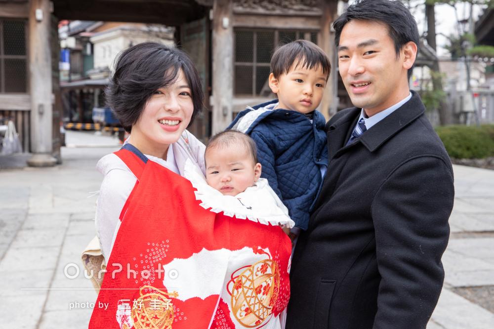 赤い産着に包まれてばっちりとカメラ目線のお宮参り写真の撮影