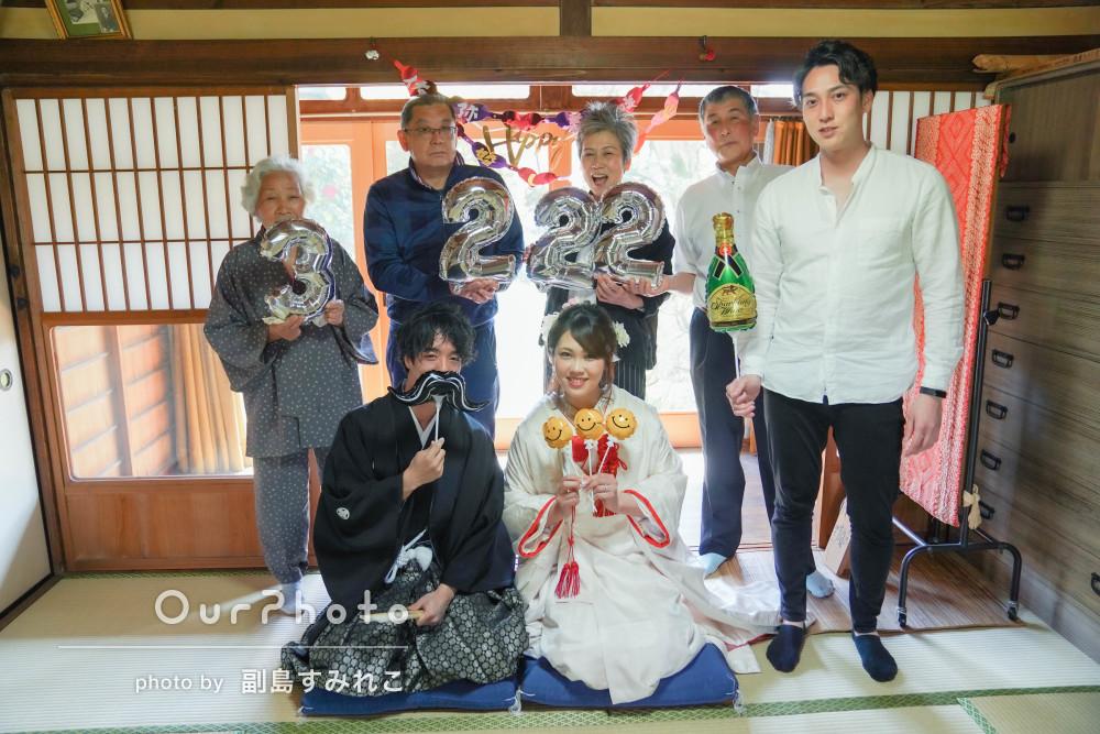 婚礼衣装に身を包む若いふたりと祝福に集まった家族の和やかな記念撮影