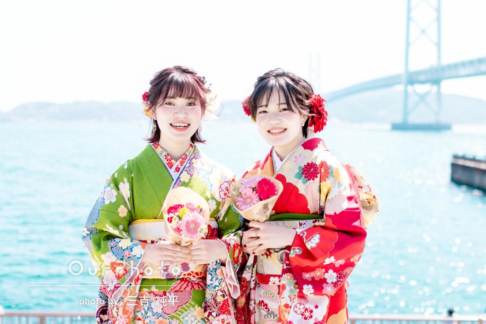 爽快な青空の下で鮮やかな振袖を着て友人と2人で成人式の前撮りの撮影