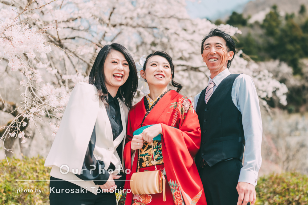 しだれ桜を眺めながらクールな印象の振り袖姿で両親と成人式の撮影