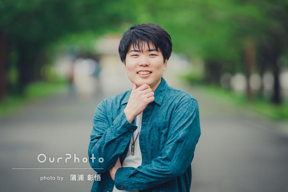 緑の並木道をバックに優しい笑顔が素敵な男性プロフィール写真の撮影