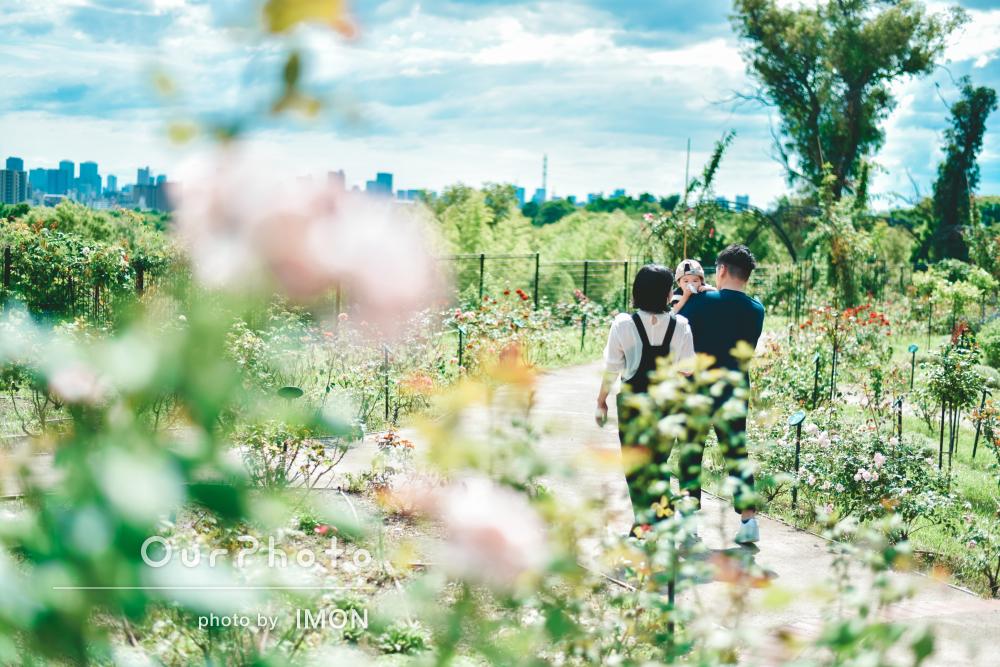 青い空に色鮮やかな花や緑が広がる公園で楽しそうな家族写真の撮影