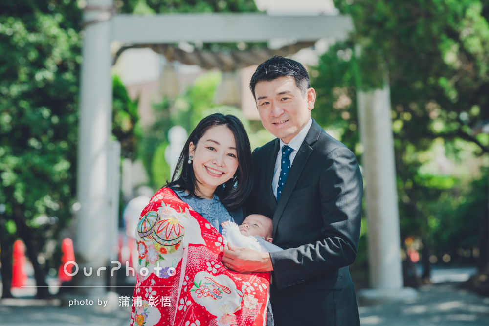 緑豊かな神社でパパとママに抱っこしてもらい幸せそうなお宮参りの撮影