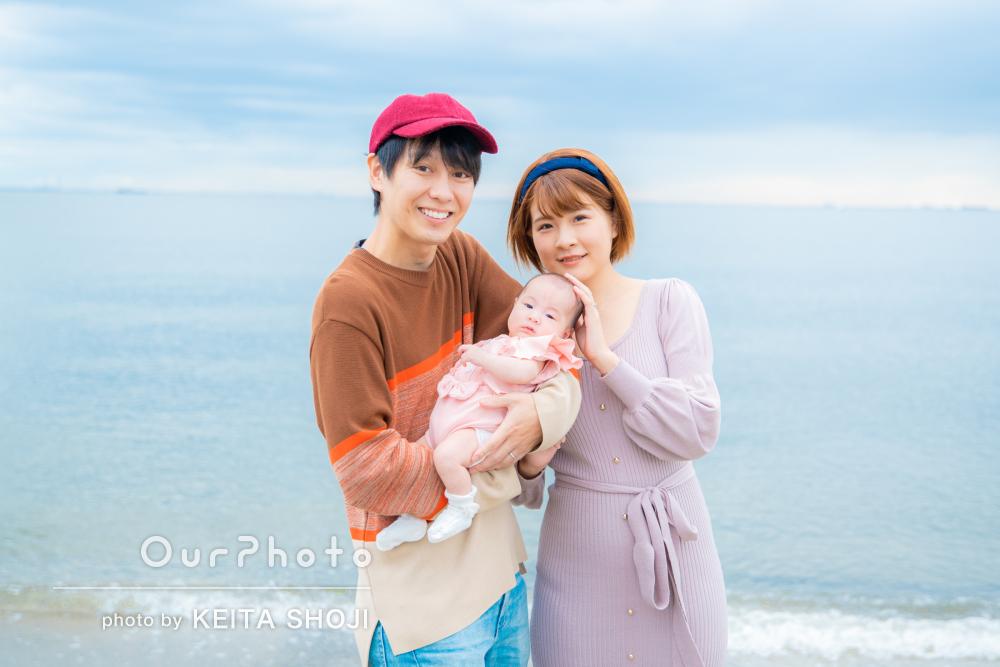 赤ちゃんと両親の3人で海辺の公園で暖かく微笑ましい家族写真の撮影