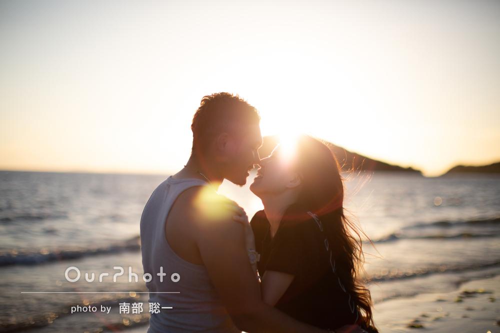夕日をバックにビーチでロマンチックなカップルフォトの撮影