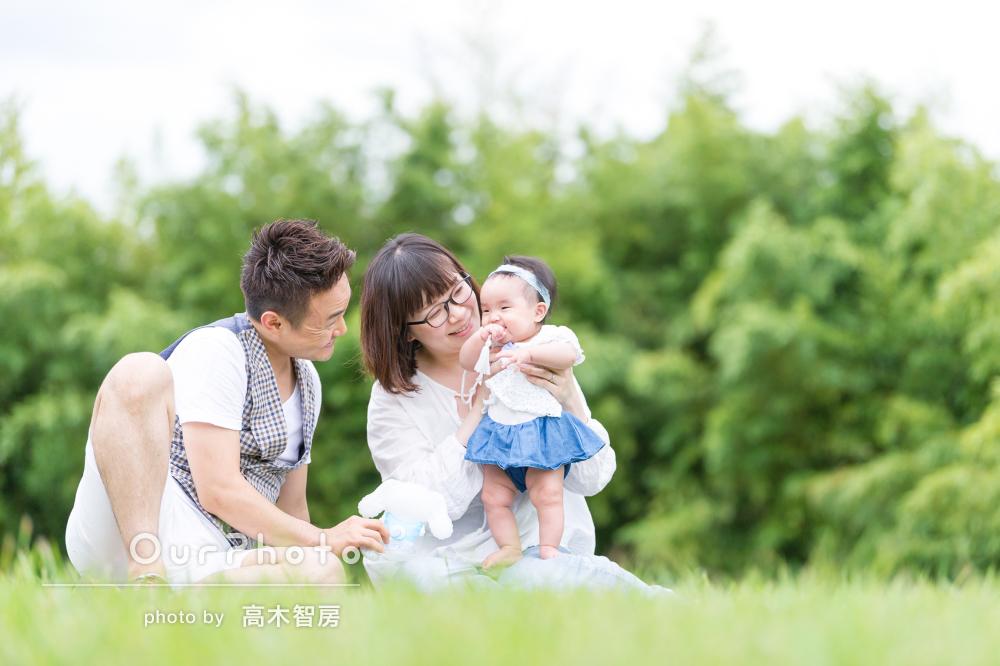 緑や花に囲まれたハーフバースデイ記念のカジュアル家族写真