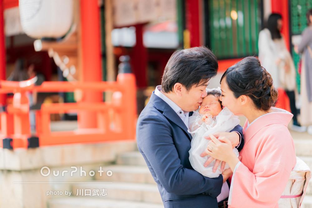 神社の赤と緑に優しい笑顔が印象的なお宮参りの写真の撮影