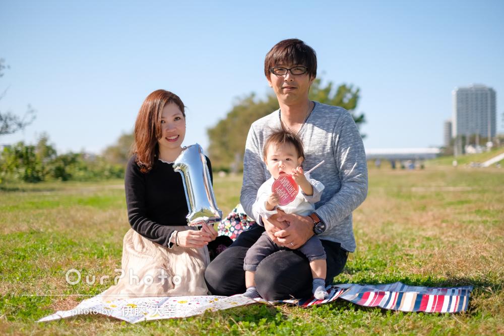 青空の下一瞬の笑顔も逃さない1歳の誕生日記念の家族写真の撮影