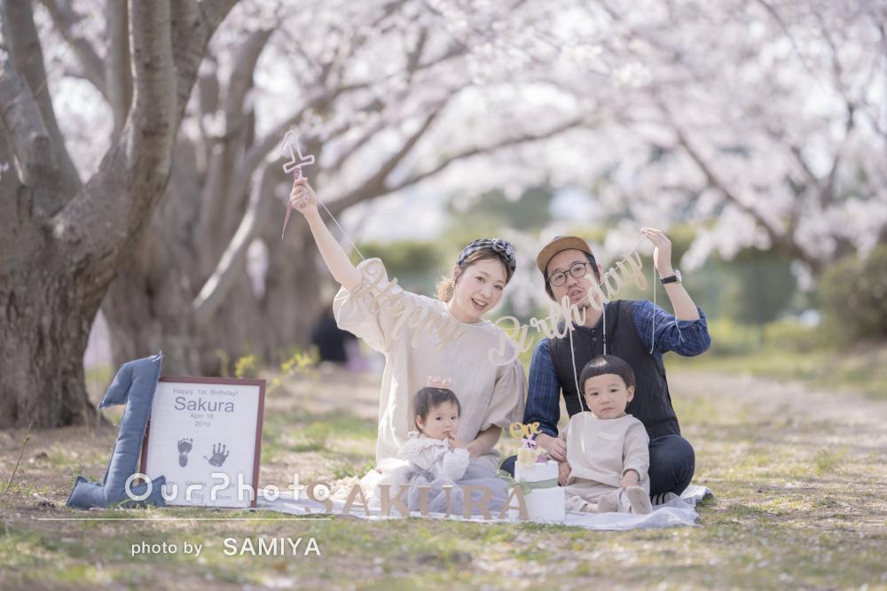 桜を背景に1歳誕生日を記念した優しい雰囲気の家族写真