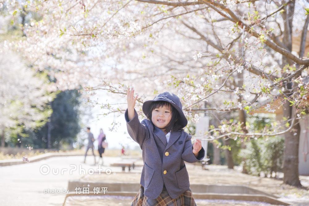春の光の中で桜を背景に自然な表情の入園記念の家族写真