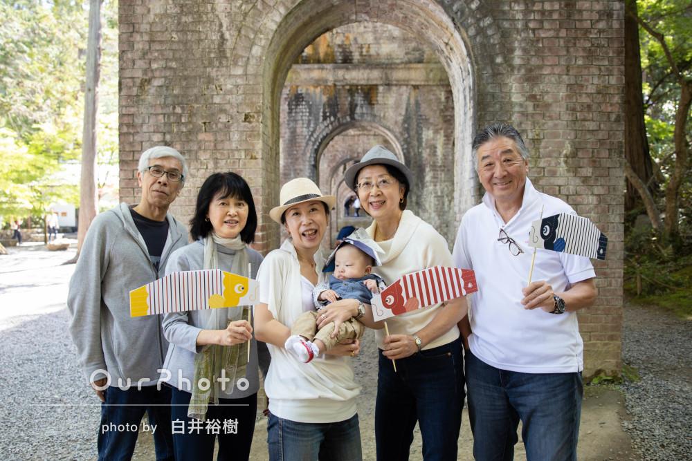 新聞紙の兜とカラフルな鯉のぼりで初節句記念の家族写真