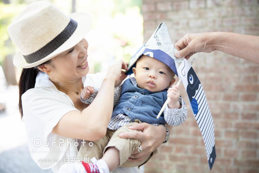 新聞紙の兜と小道具の鯉のぼりで初節句記念の家族写真