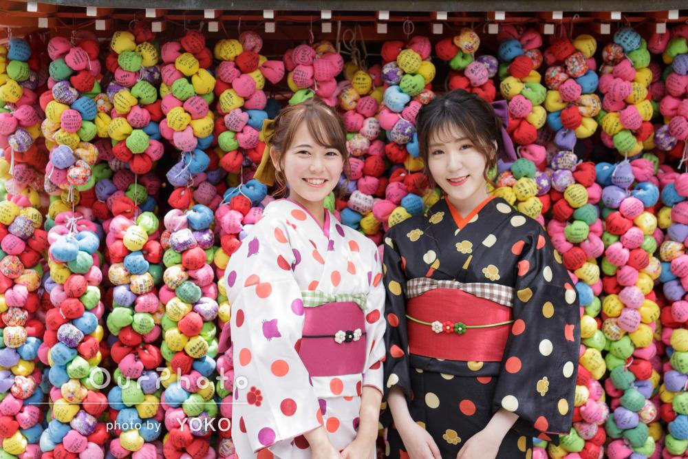 趣ある京都の町で、鮮やかなお揃い着物で友人と仲良く写真撮影