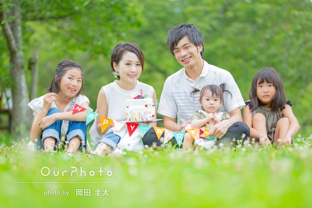 緑に囲まれ、にこにこ笑顔の仲良し家族の記念写真の撮影
