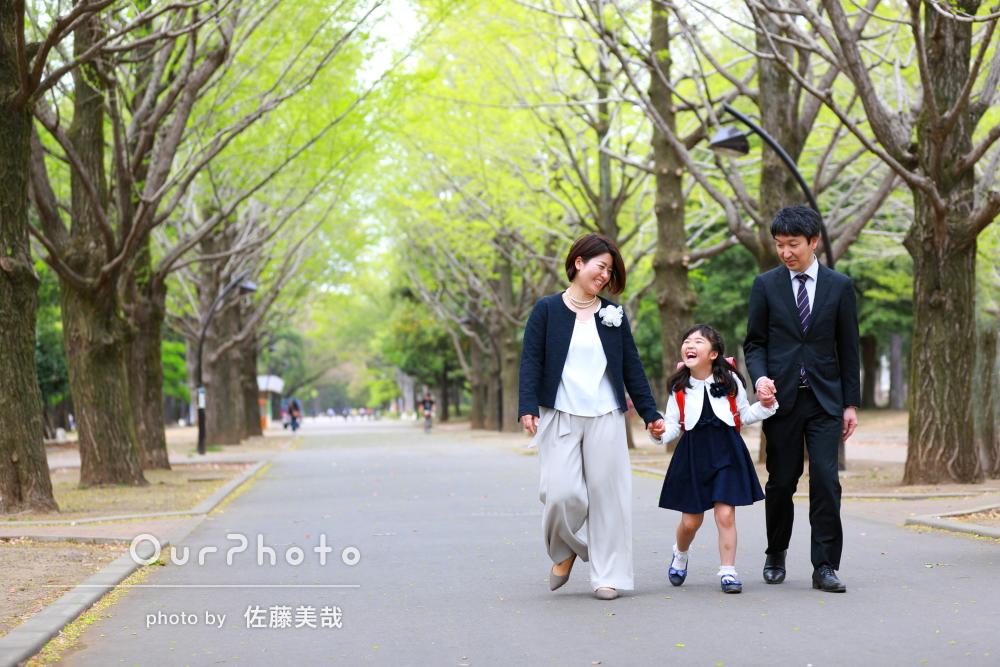 家族3人で並木道を歩く幸せそうな写真