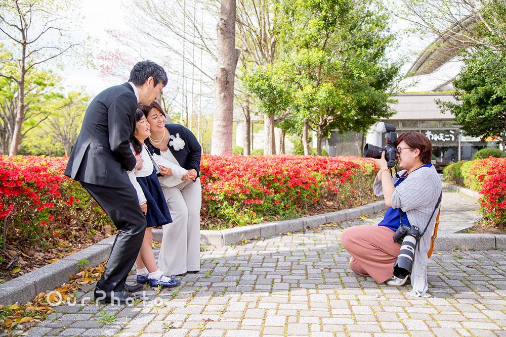 綺麗な花壇前で家族3人を撮影している風景