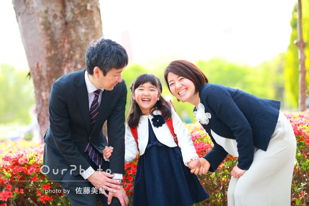 花壇の前で幸せそうに笑う家族3人の写真